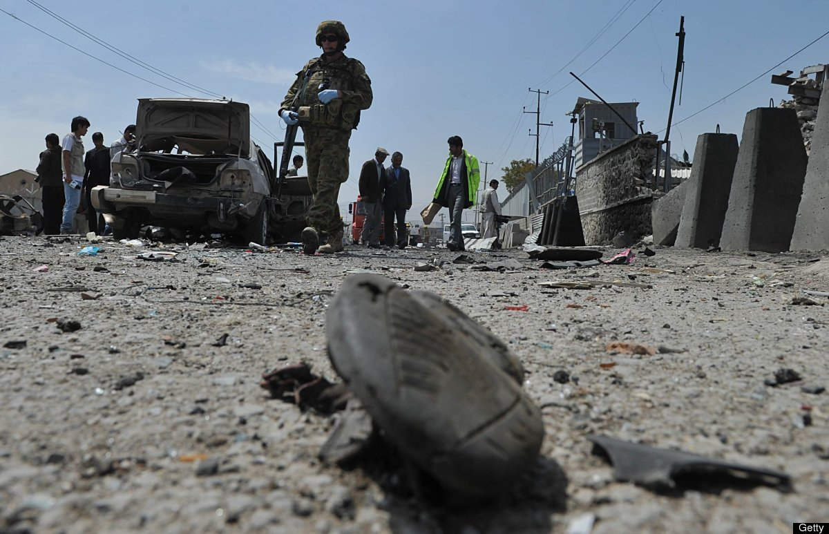 <em>A soldier of the NATO-led International Security Assistance Force (ISAF) walks at the site of a suicide attack in front o