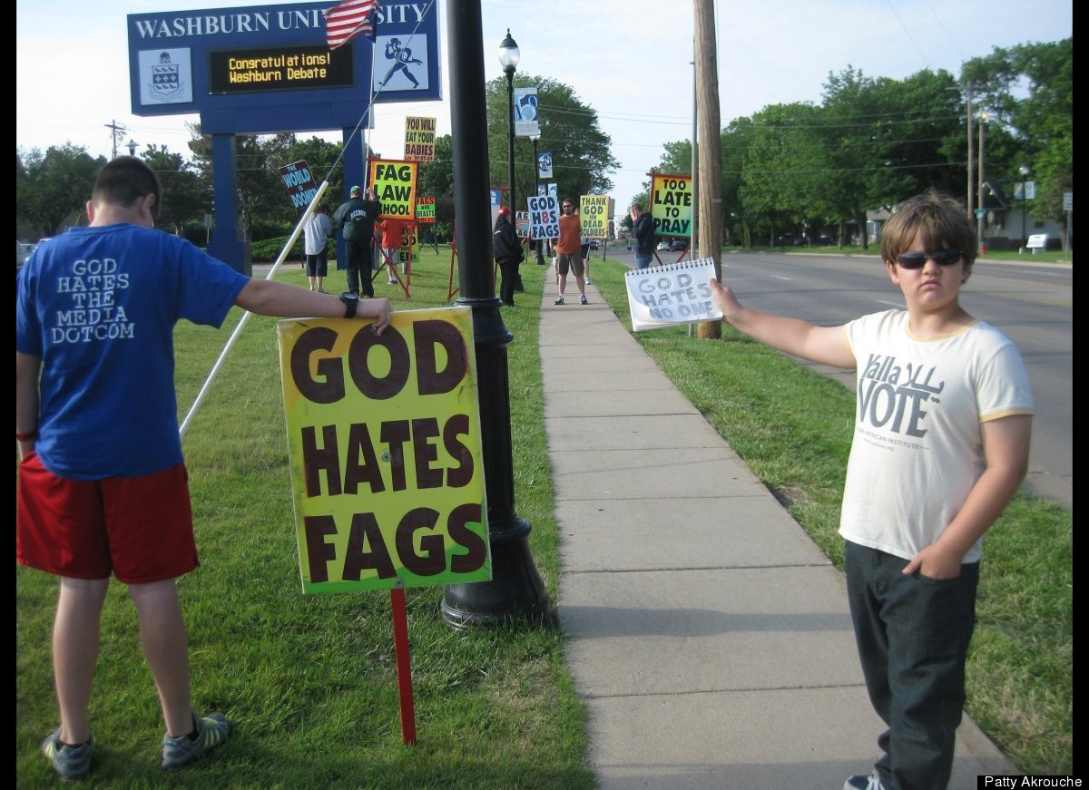 """Jose Miles holds up a sign that reads """"God Hates No One"""" as the Westboro Baptist Church protests at Washburn University in To"""