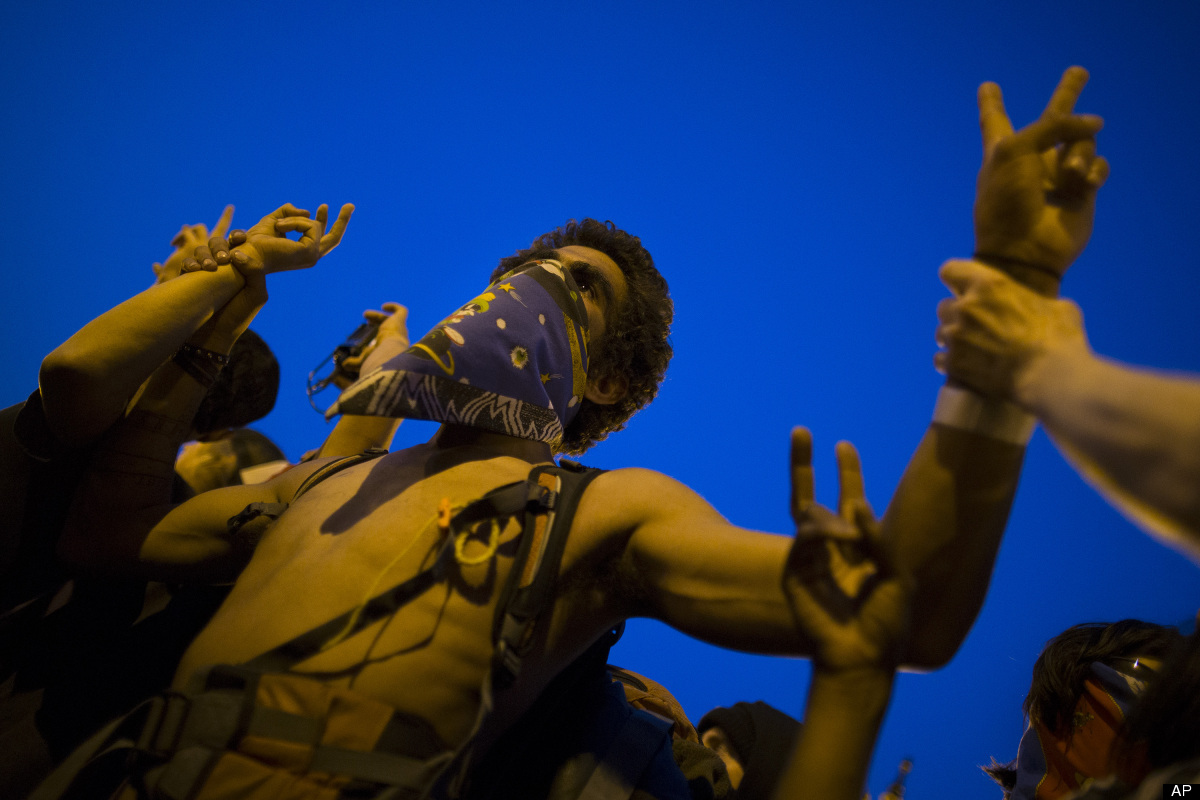 An anti-NATO protestor flashes peace signs during a march, Saturday, May 19, 2012, in Chicago. On Sunday, the start of the tw