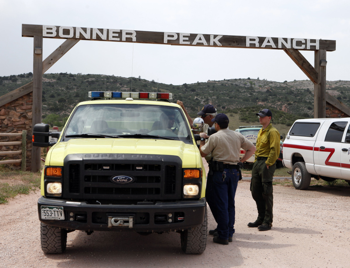 Sheriff's deputies block the entrance to the Bonner Peak Ranch residendial area northwest of Fort Collins, Colo., on Thursday