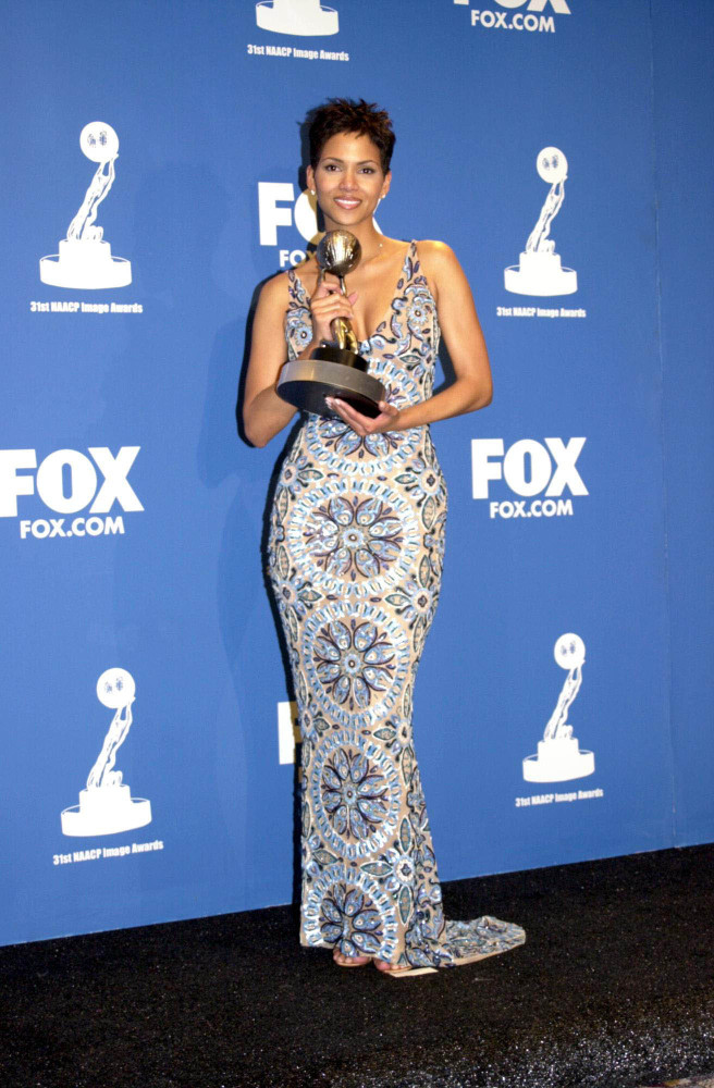 Halle Berry poses for photos wearing a patterned dress.