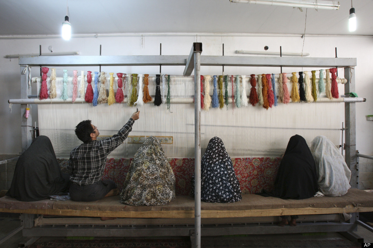<em>In this Saturday, Nov. 12, 2011 photo, Iranian women and a man weave carpet in a workshop in Qom, 78 miles (125 kilometer