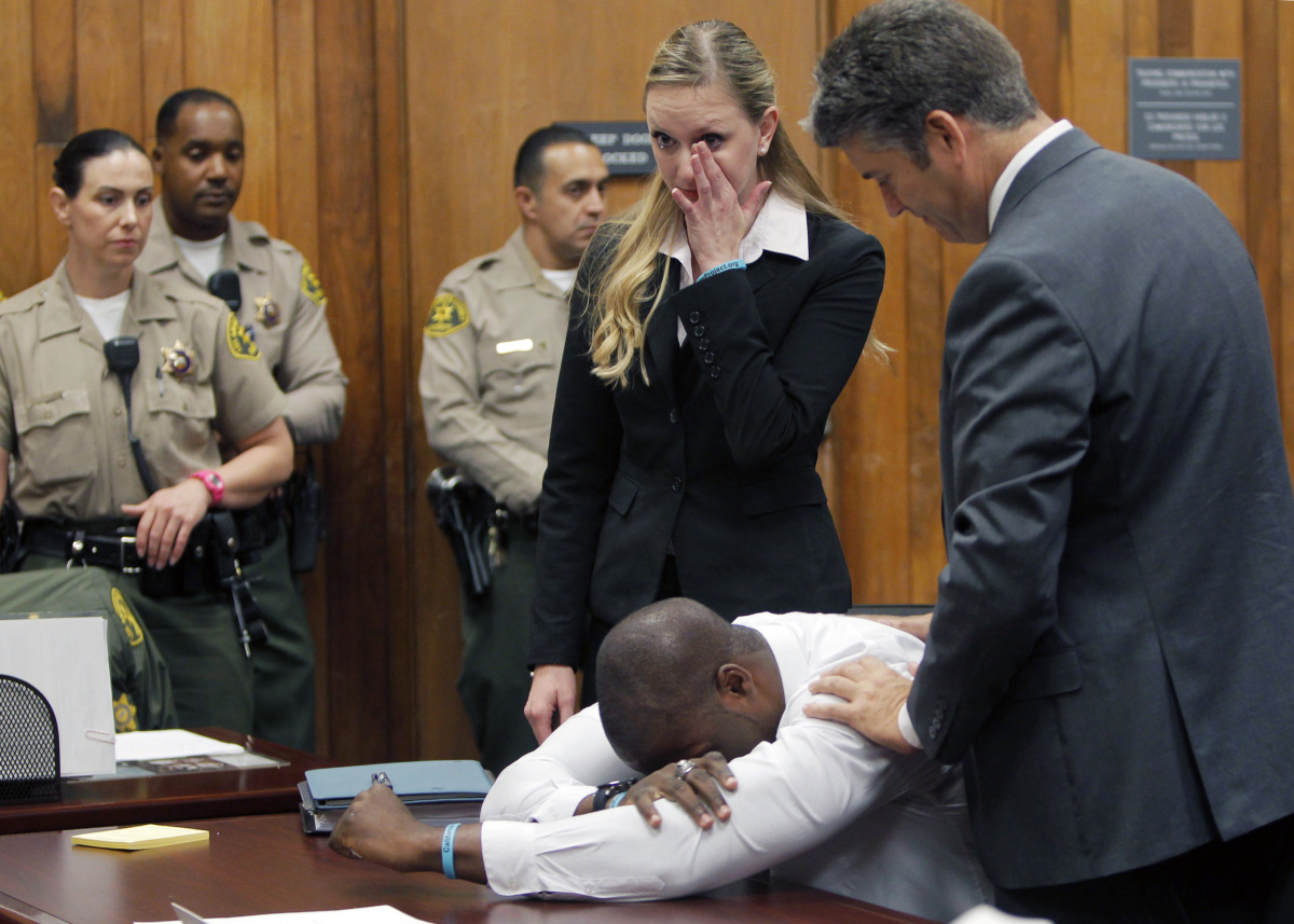 Brian Banks becomes emotional as his attorney Justin Brooks, right, and attorney Alissa Bjerkhoel stand by, as Banks' rape co