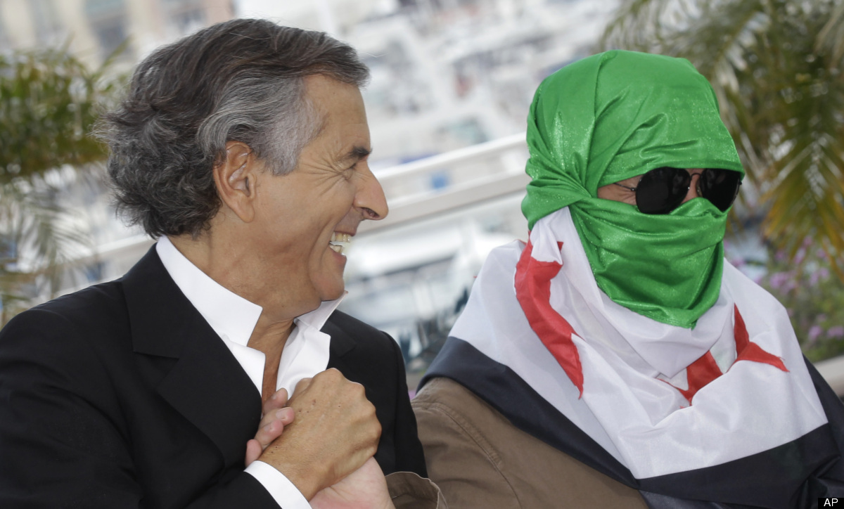 Director Bernard-Henry Levy, left, and an unidentified person wearing a Syrian flag pose during a photo call for The Oath of