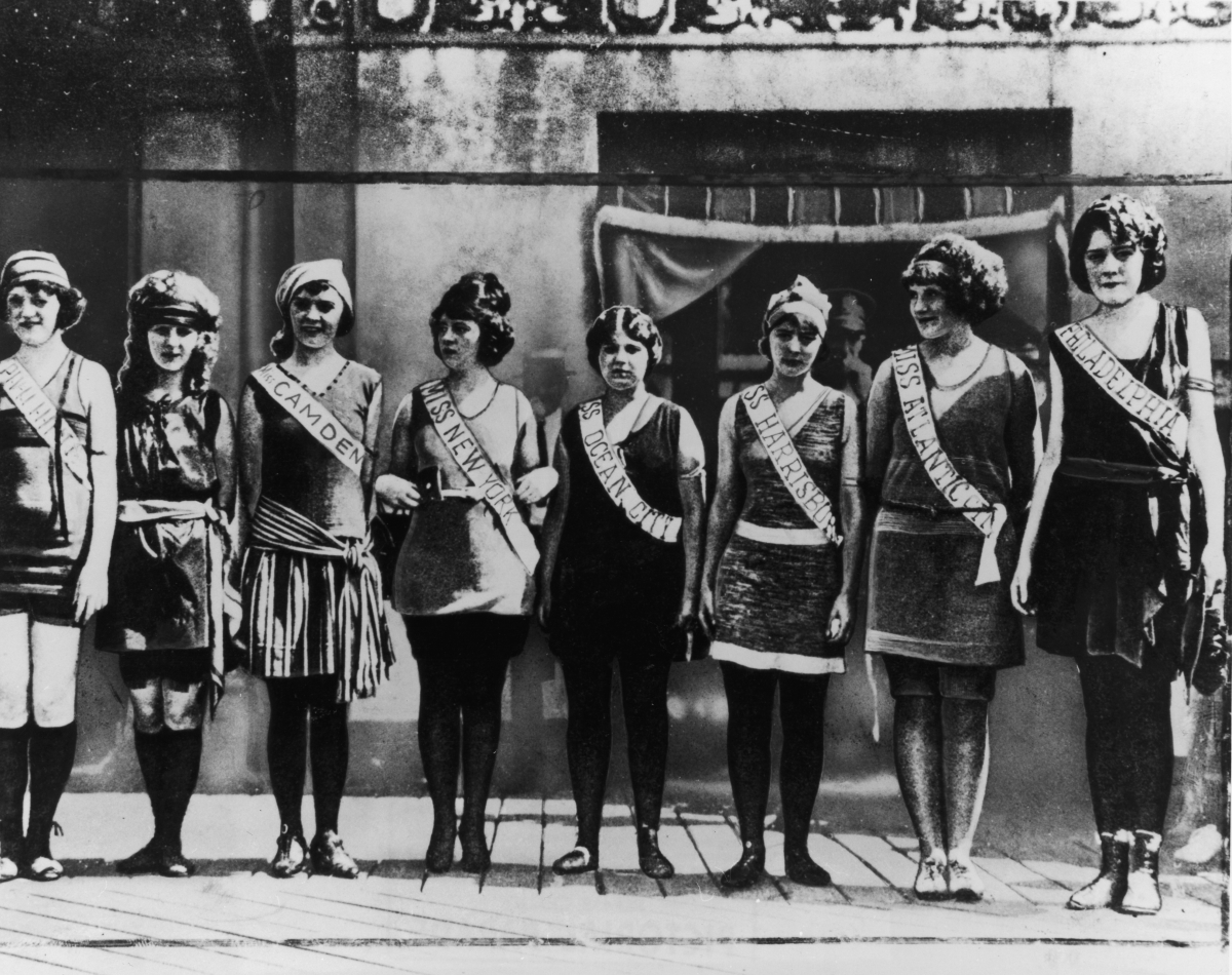 1921:  Full-length portrait of the first Miss America contestants, wearing their sashes over swimsuits, standing in a line on