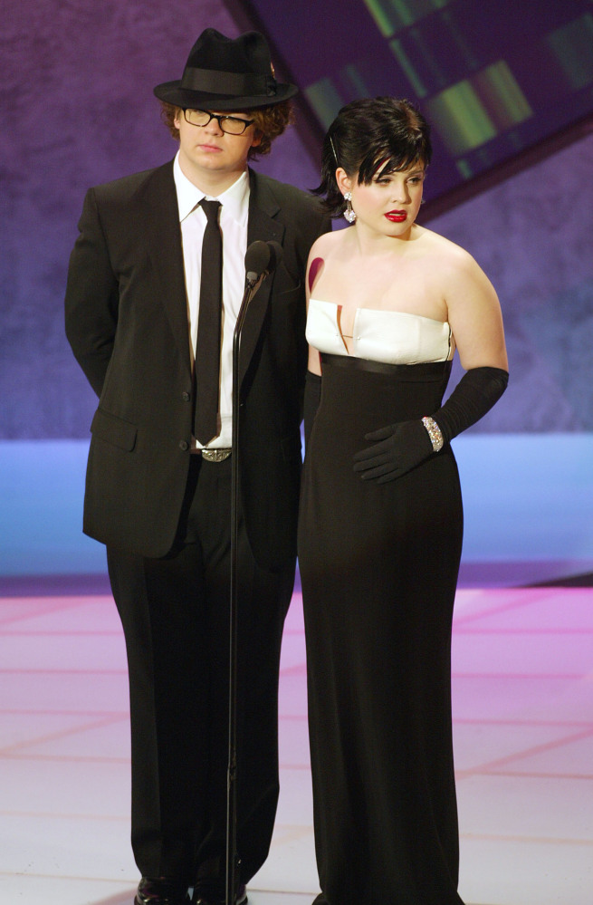 Jack and Kelly Osbourne on stage. Kelly wears a floor-length gown with pearls reminiscent of Audrey Hepburn.
