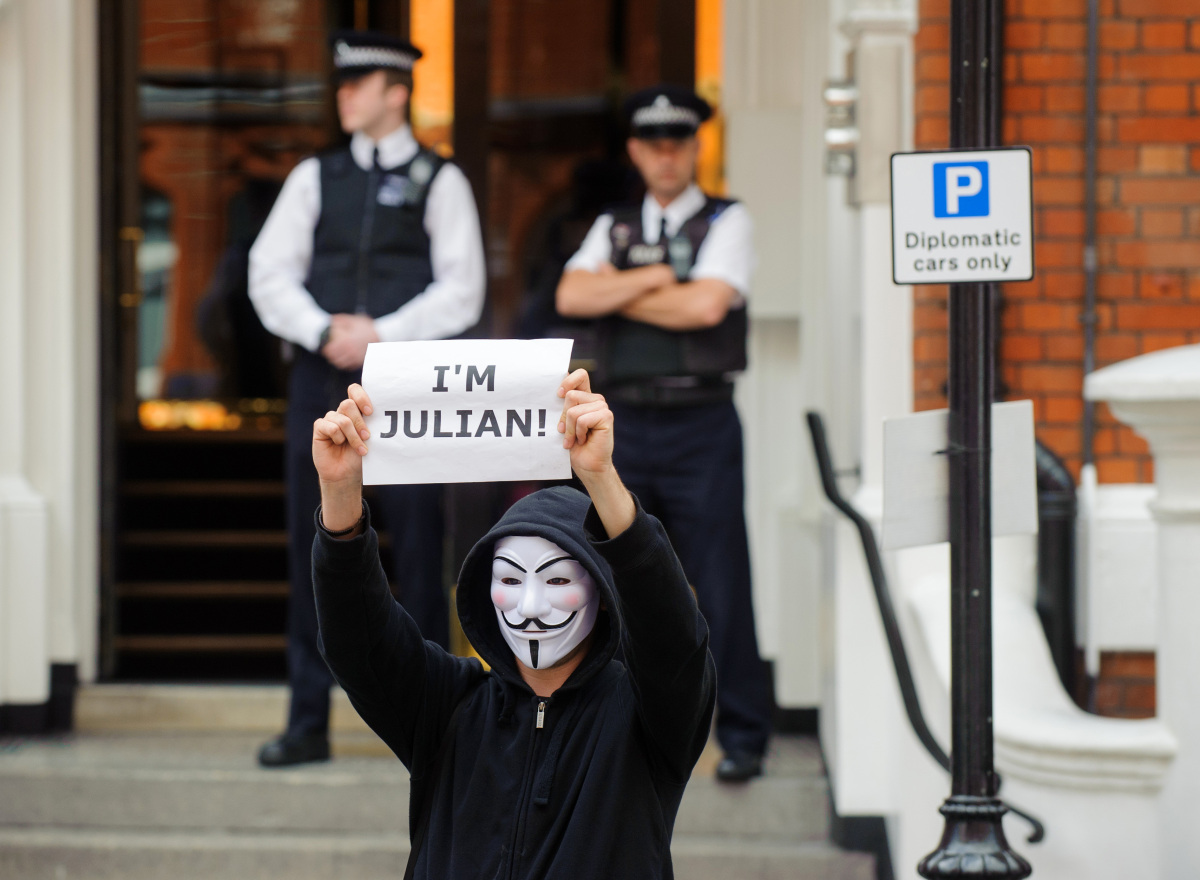 A masked supporter of Julian Assange outside the Embassy of Ecuador in Knightsbridge, central London, as the diplomatic row b
