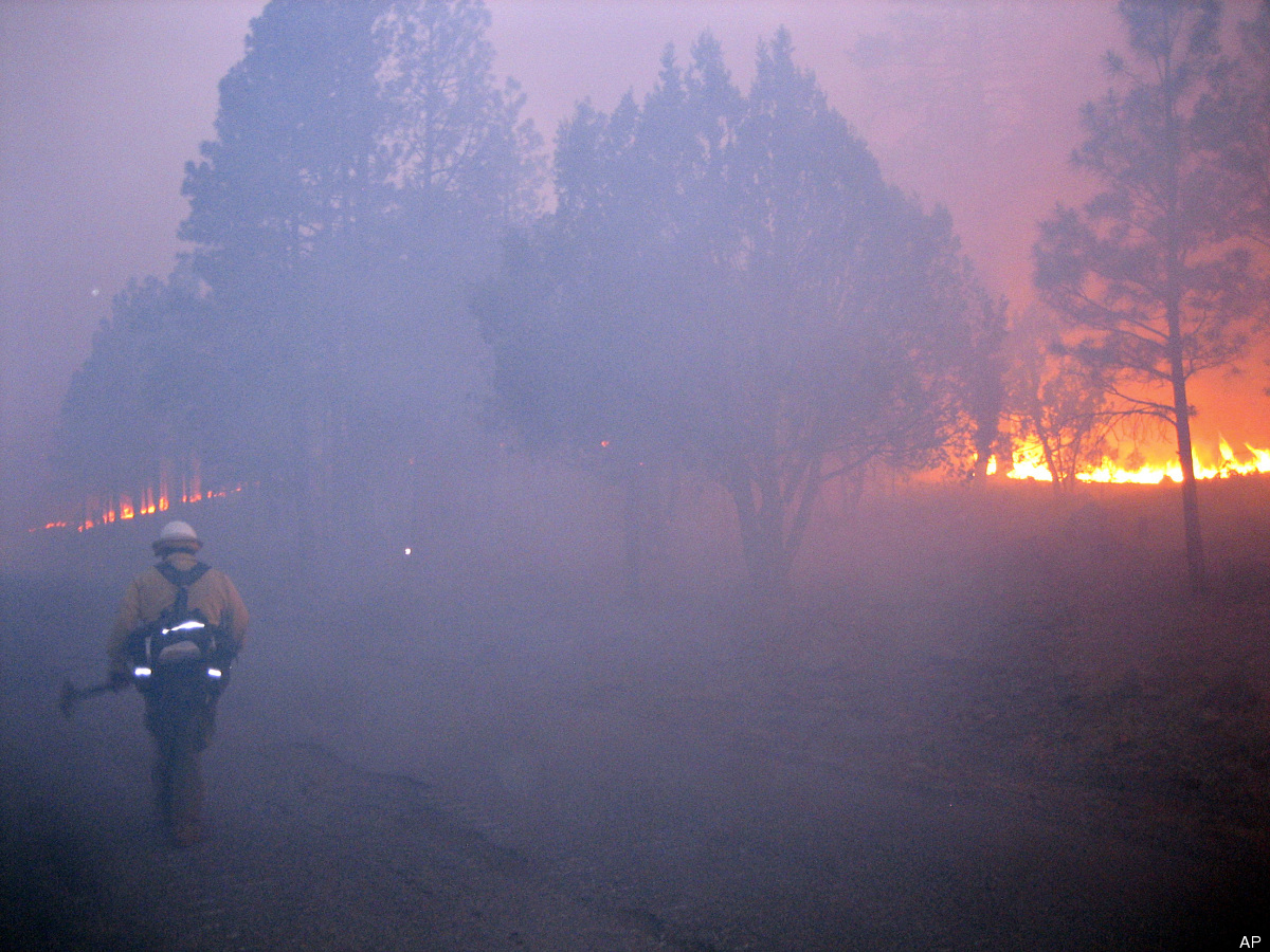 In this Tuesday, May 29, 2012 photo provided by the U.S. Forest Service, a firefighter walks along a burn out line as part of