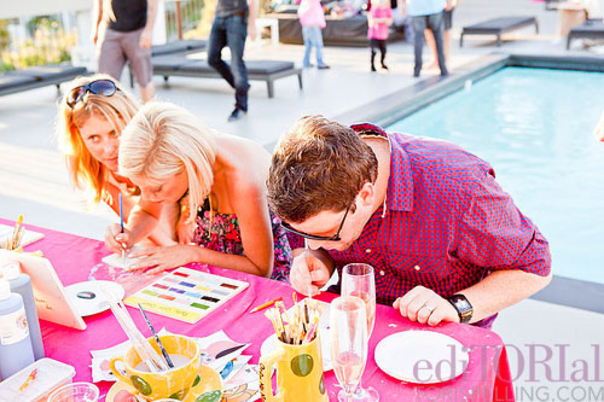 Husband and wife, Tori and Dean, intently work on a craft project poolside.