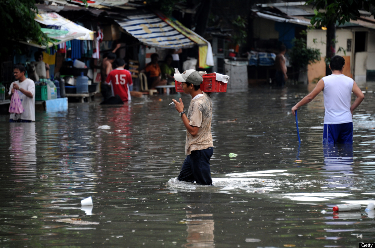 Residents are seen in a flooded street after a heavy rain in Manila on May 31, 2012.  Clogged drainage system is often blamed