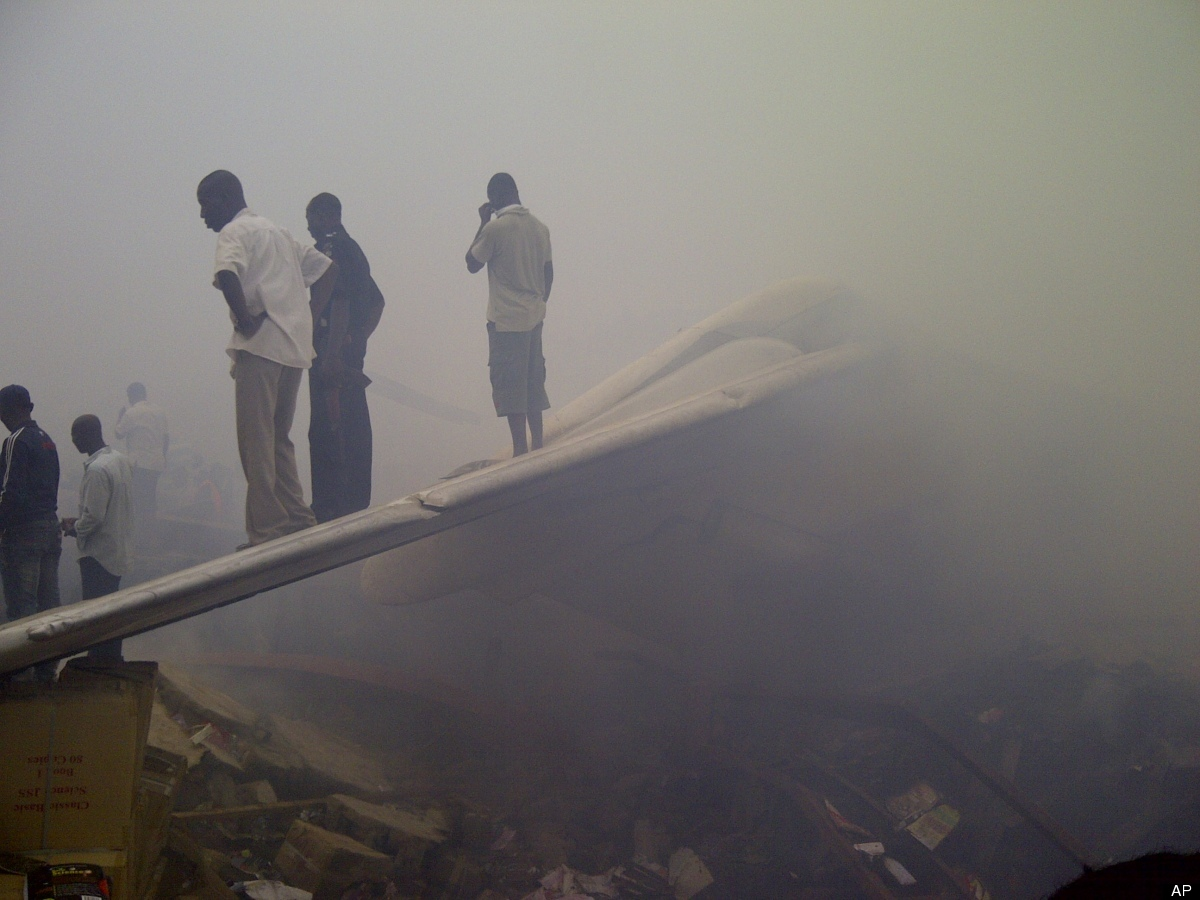 Onlookers stand on the tail wing of a crashed passenger plane in a neighborhood just north of Murtala Muhammed International