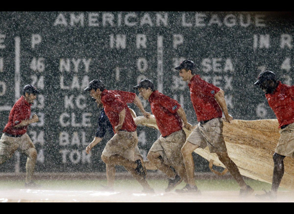 Grounds crew members quickly pull the tarp onto the field during a heavy rain in the eighth inning of a baseball game between