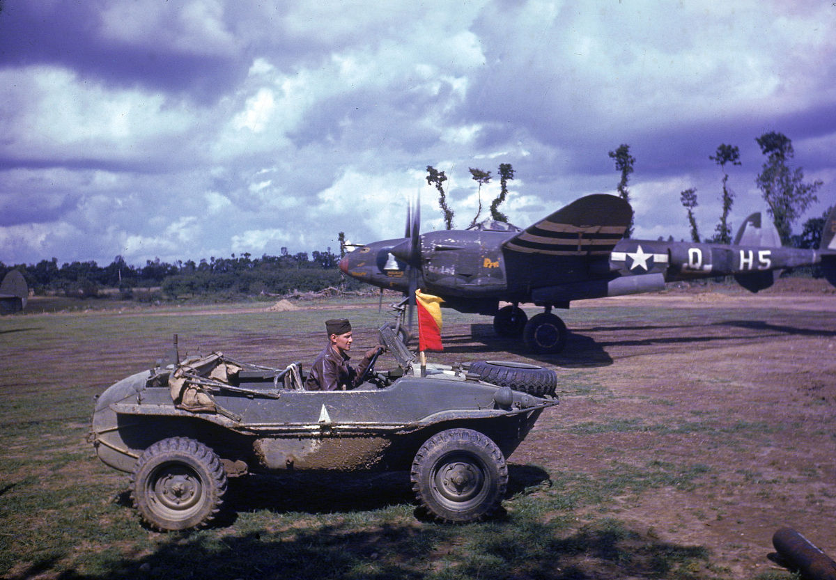 P38 fighter getting ready to fly a mission as the pilot arrives in a captured German vehicle shortly after the  liberation of