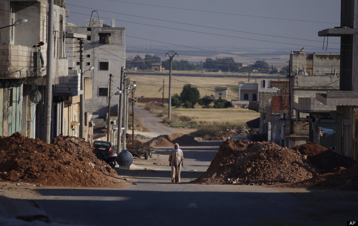A Syrian man walks between piles of dirt left by the pro-Assad army on the sides of a street in the town of Taftanaz, 15 km e