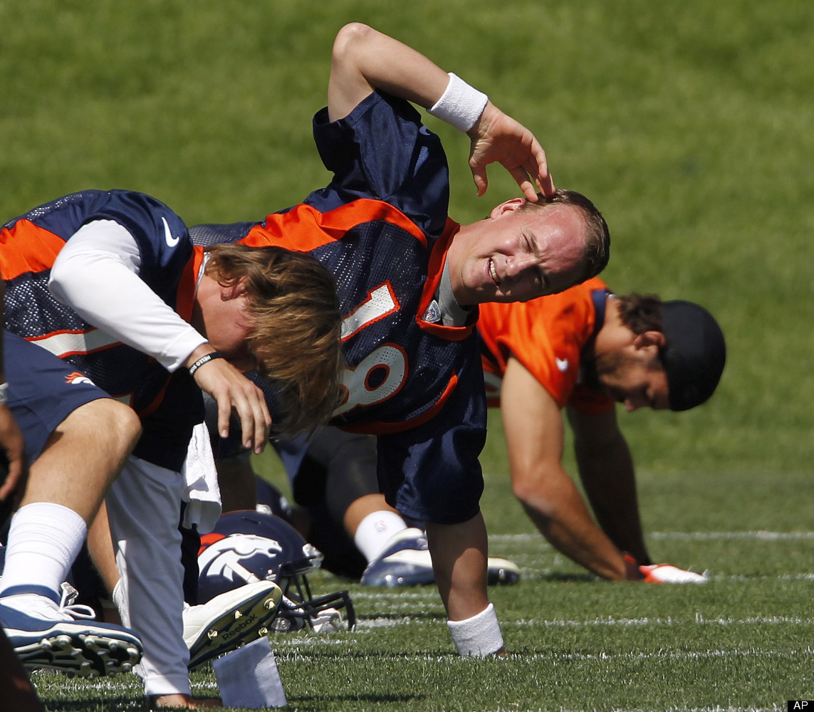 Denver Broncos quarterback Peyton Manning (18) stretches with teammates at NFL football practice at the team's training facil