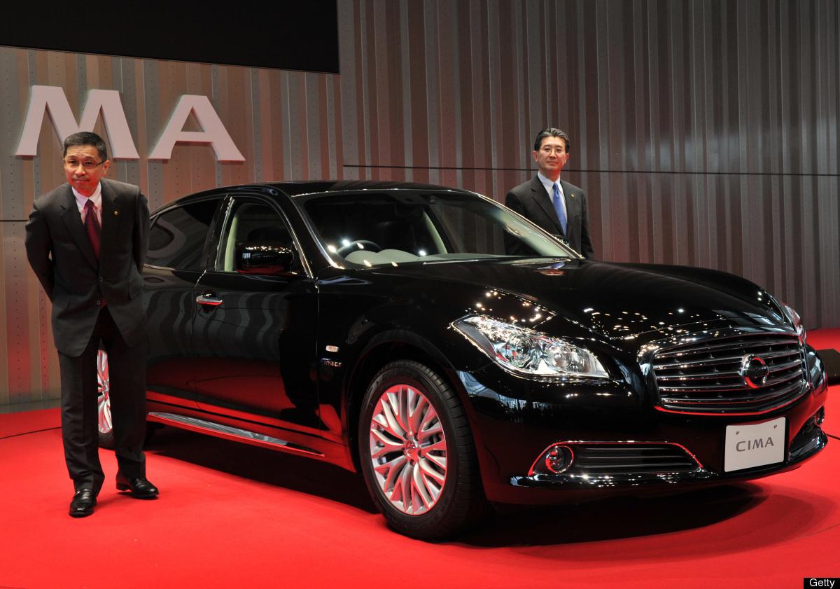 Japan's auto giant Nissan Motor executive vice president Hiroto Saikawa (L) displays the company's new luxury sedan 'Cima', w