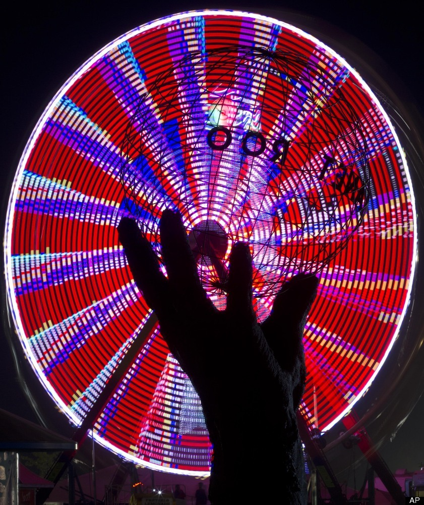 A time lapse photo puts bright colors from the ferris wheel spinning behind the Planet Roo statue during the Bonnaroo Music a