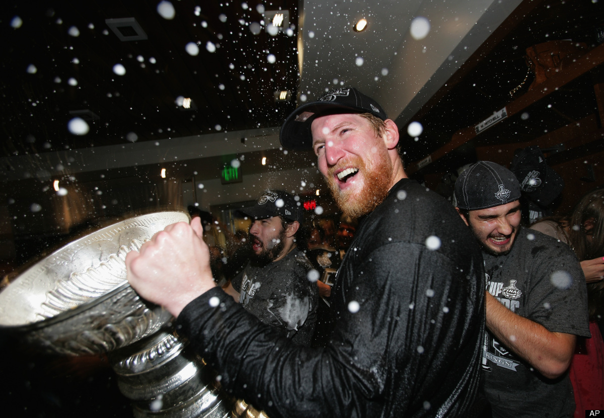 Los Angeles Kings defenseman Matt Greene (2) celebrates with the Stanley Cup in the locker room after the Kings defeated the