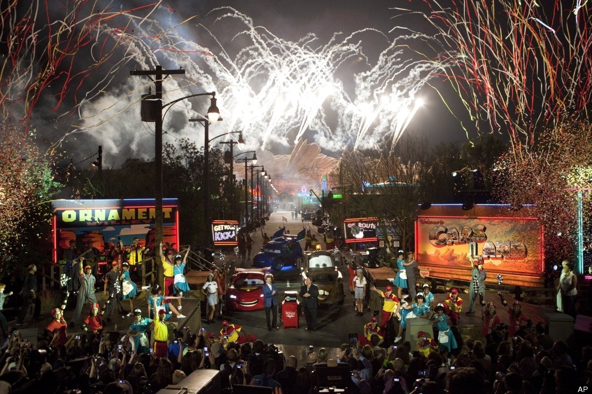 Confetti cascades while rows of bright neon signs, illuminated billboards and pyrotechnics light up the sky. (AP Photo/Scott