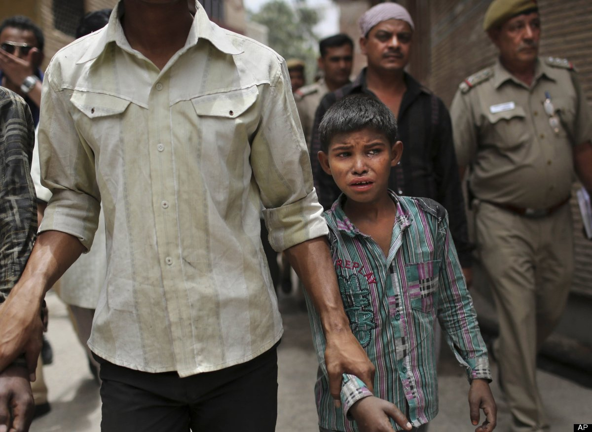 A young Indian bonded child laborer cries as he is walked away after being rescued during a raid by workers from Bachpan Bach