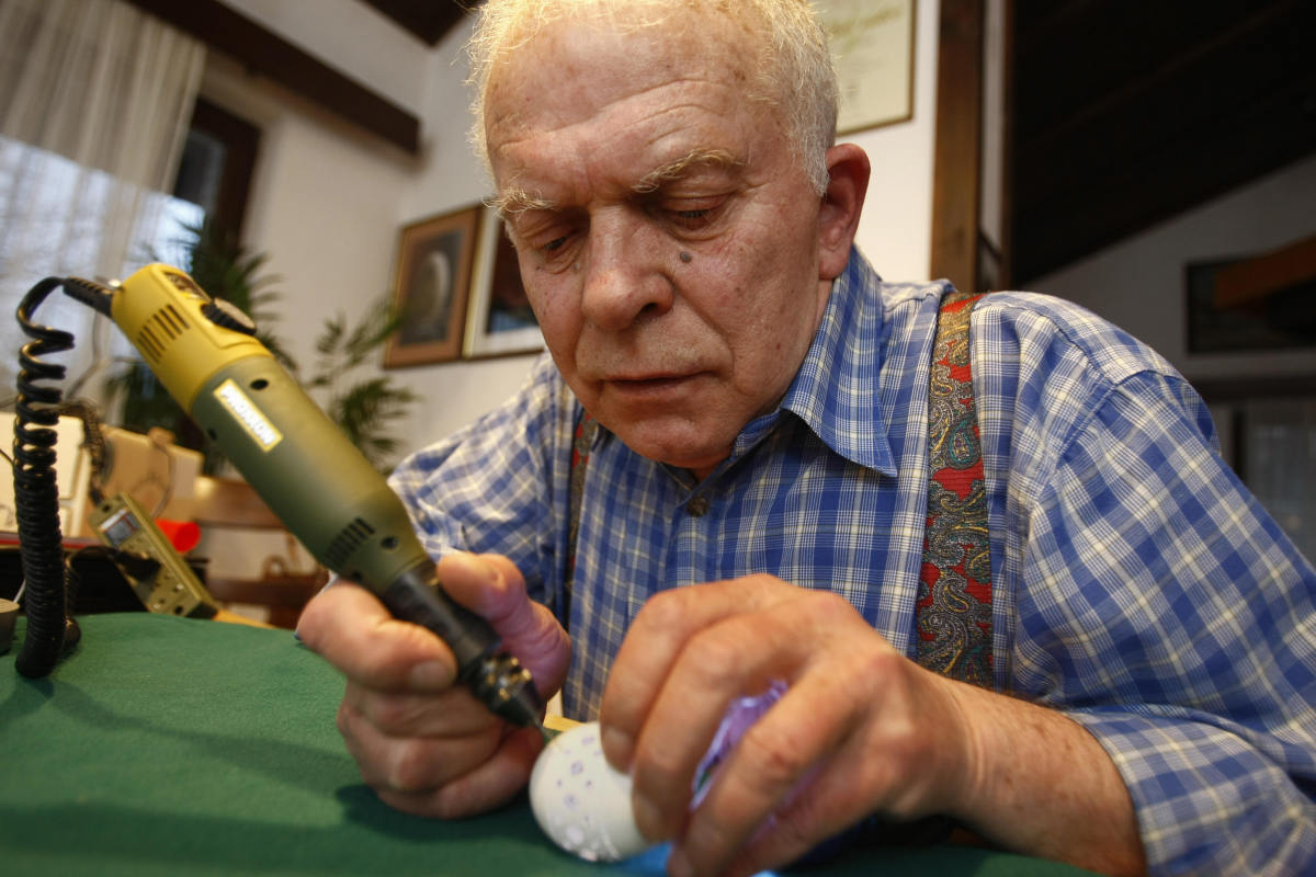 Slovenian craftsman Franc Grom drills hole at one of his special Easter eggshells with ornamented holes on it. He drills an a