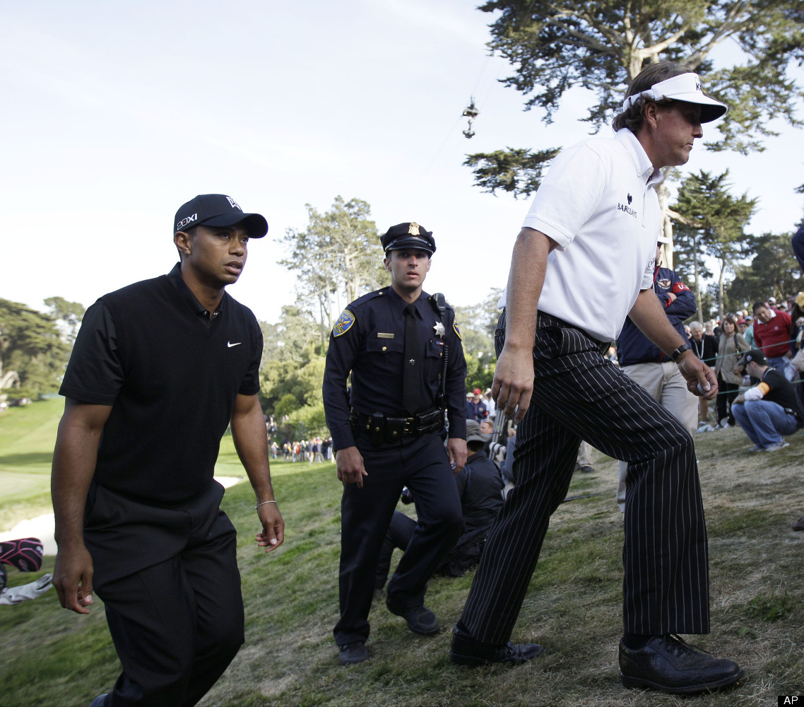 Tiger Woods and Phil Mickelson walk off the 18th green after the second round of the U.S. Open Championship golf tournament F