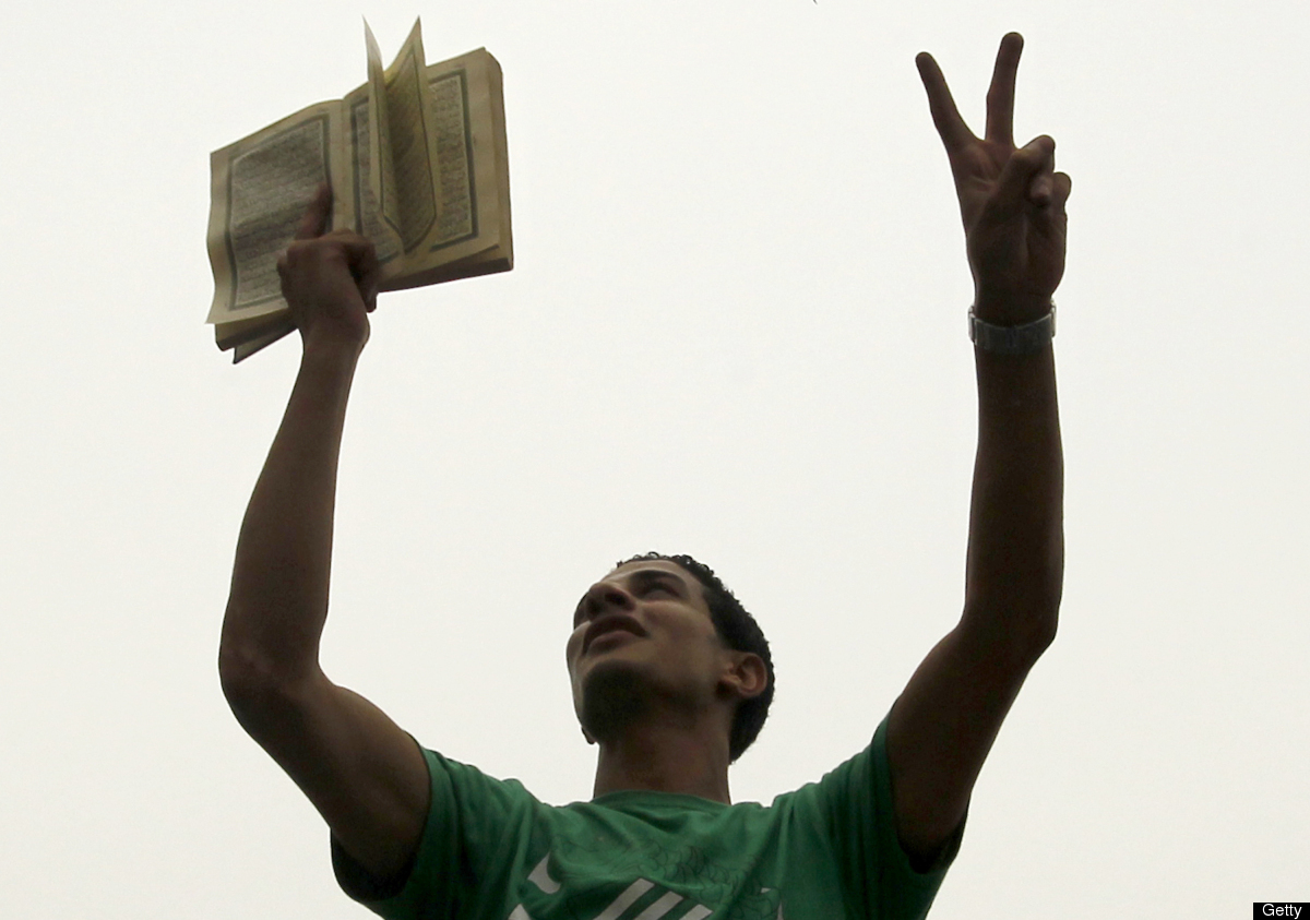 A supporter of Muslim Brotherhood candidate Mohammed Mursi flashes the sign for victory as holds up a Koran, Islam's holy boo
