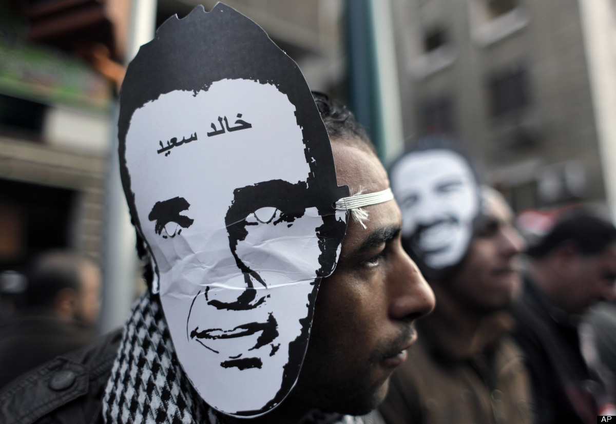 FILE - In this Monday, Jan. 23, 2012 file photo, Egyptian protesters, one wearing a mask depicting slain Egyptian activist Kh