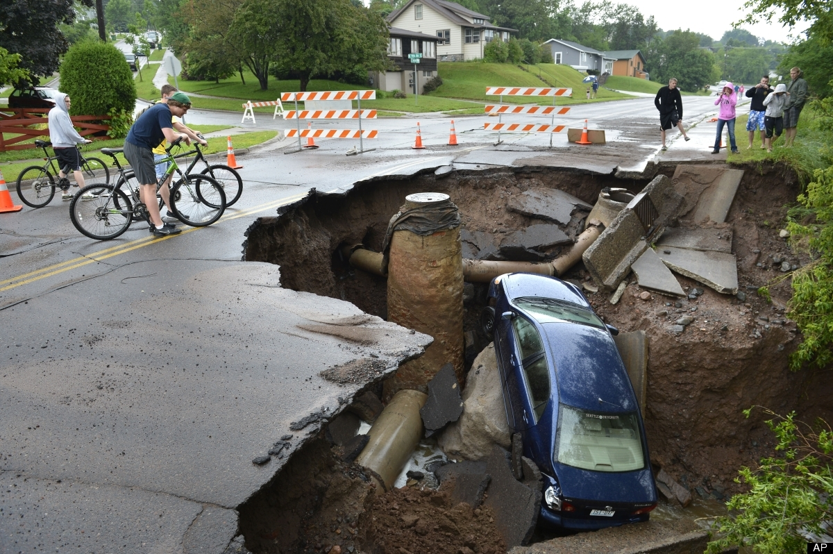 A car sits in a giant sinkhole in Duluth, Minn. Wednesday, June 20, 2011. Residents evacuated their homes and animals escaped