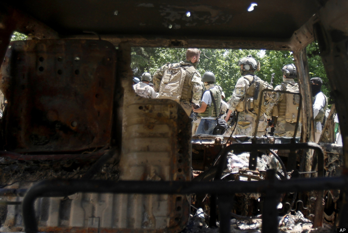 Soldiers from NATO-led forces are seen through the remains of a burnt vehicle outside the Spozhmai hotel on Lake Qargha where
