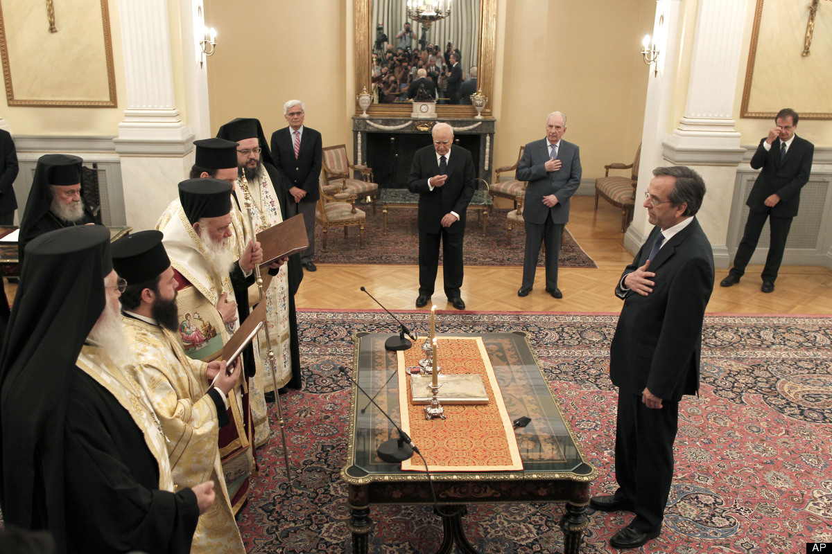 Greek conservative leader Antonis Samaras, right, crosses himself during a swearing-in ceremony at the Presidential Palace as