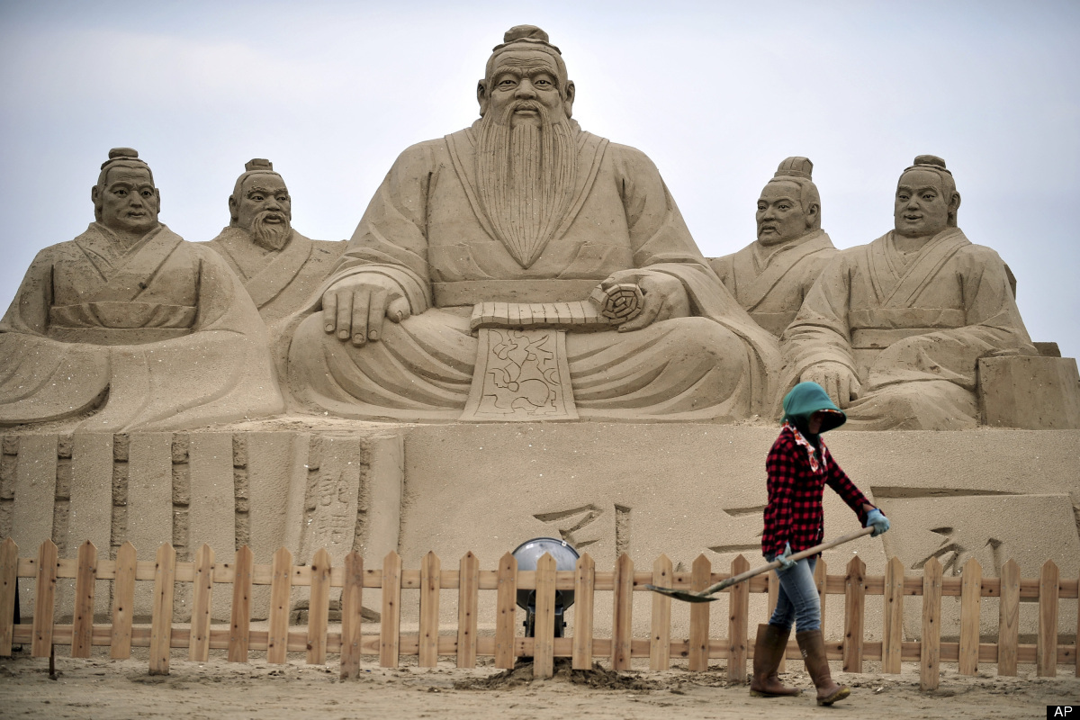 In this Sunday, June 17, 2012 photo, a woman shovels near sand sculptures of Confucius, center, a famed thinker and philosoph