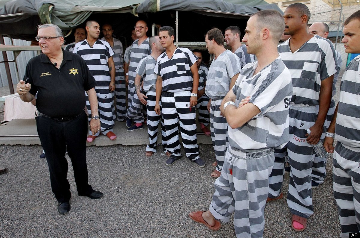 Inmates gather next to Maricopa County Sheriff Joe Arpaio as he walks through a Maricopa County Sheriff's Office jail called