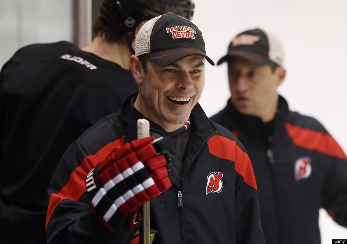 Assistant coach Adam Oates of the New Jersey Devils watches from the bench during the media day skate at the AmeriHealth Pavi