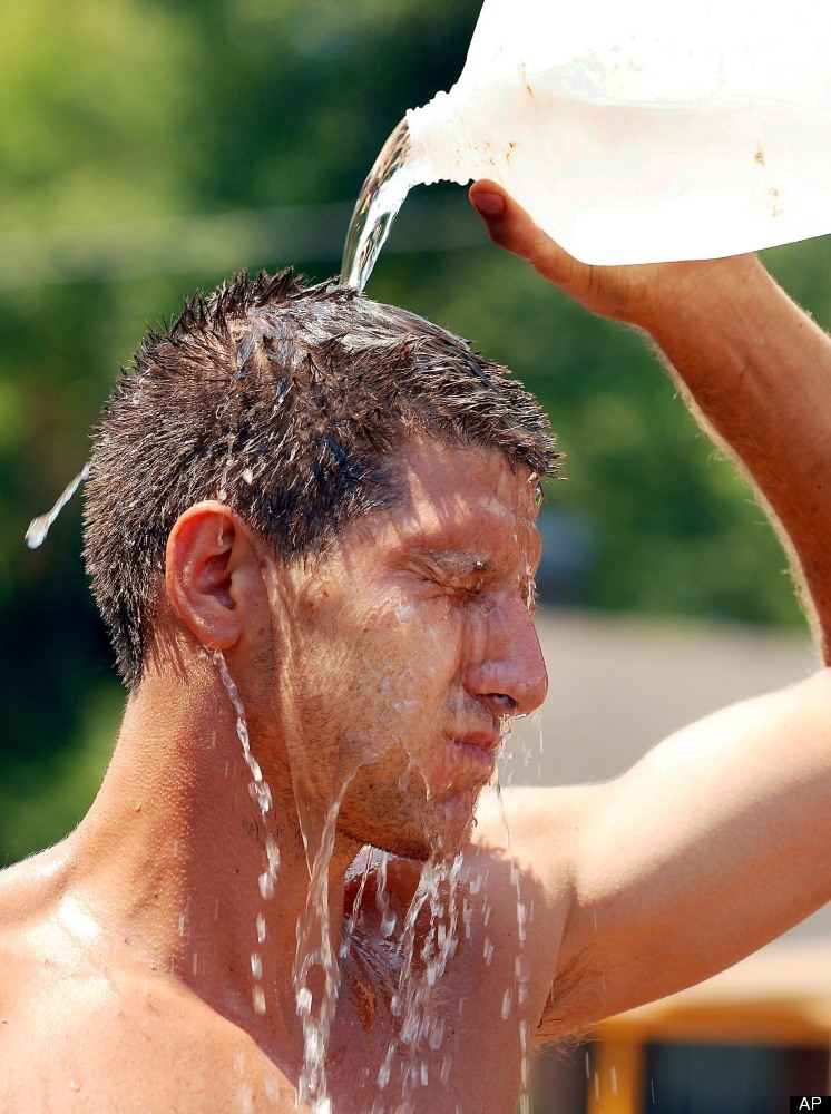 Brian Frandsen pours water over his head in an effort to cool off while building a cement block wall on Saturday, July 7, 201