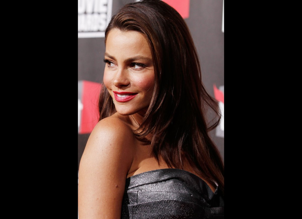 Sofia Vergara, at an award ceremony, gives a flirty grin to the cameras.