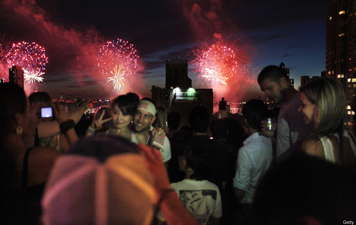 NEW YORK, NY - JULY 04:  Revelers celebrate at XVI lounge as fireworks explode over the Hudson River on July 4, 2011 in New Y
