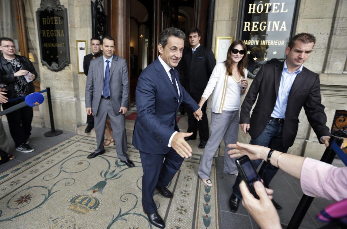 Former French president Nicolas Sarkozy (C) and his wife Carla Bruni-Sarkozy (2ndR) leave the Regina Hotel in Paris on June 2