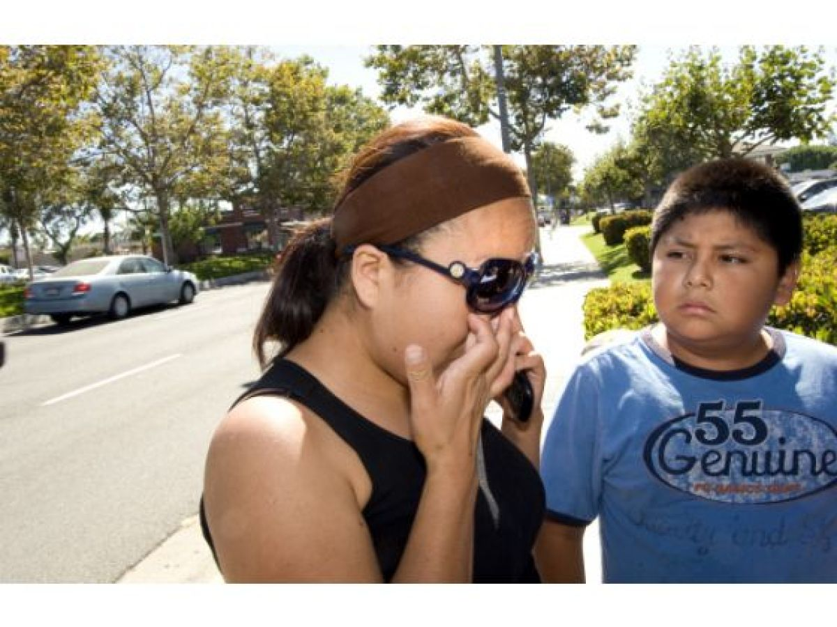 Jose Mora, 11, watches as his mother Beatriz Jimenez tries to compose herself after visiting a memorial along Santa Ana's 17t