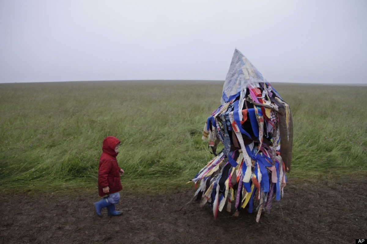 A man playing an accordion beneath a costume of torn fabrics and a child leave the Stonehenge monument in southern England, d