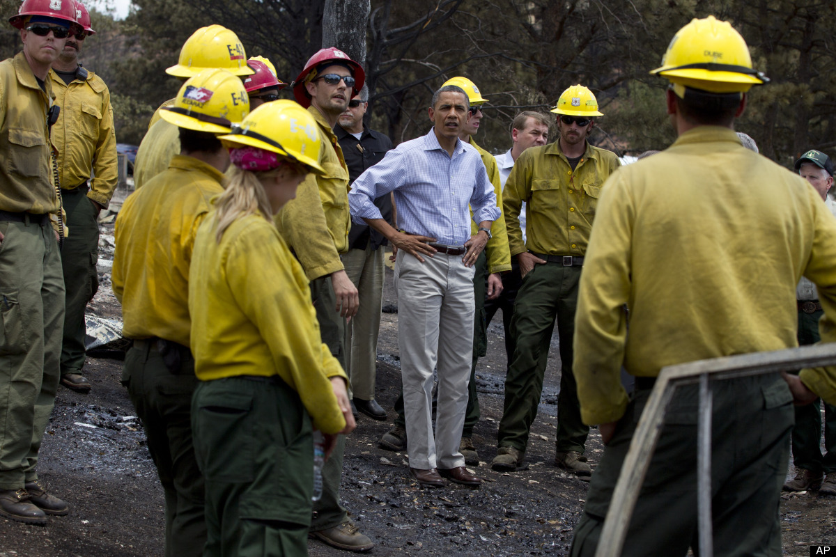 President Barack Obama talks with firefighters as he tours the Mountain Shadow neighborhood devastated by a wildfire, Friday,