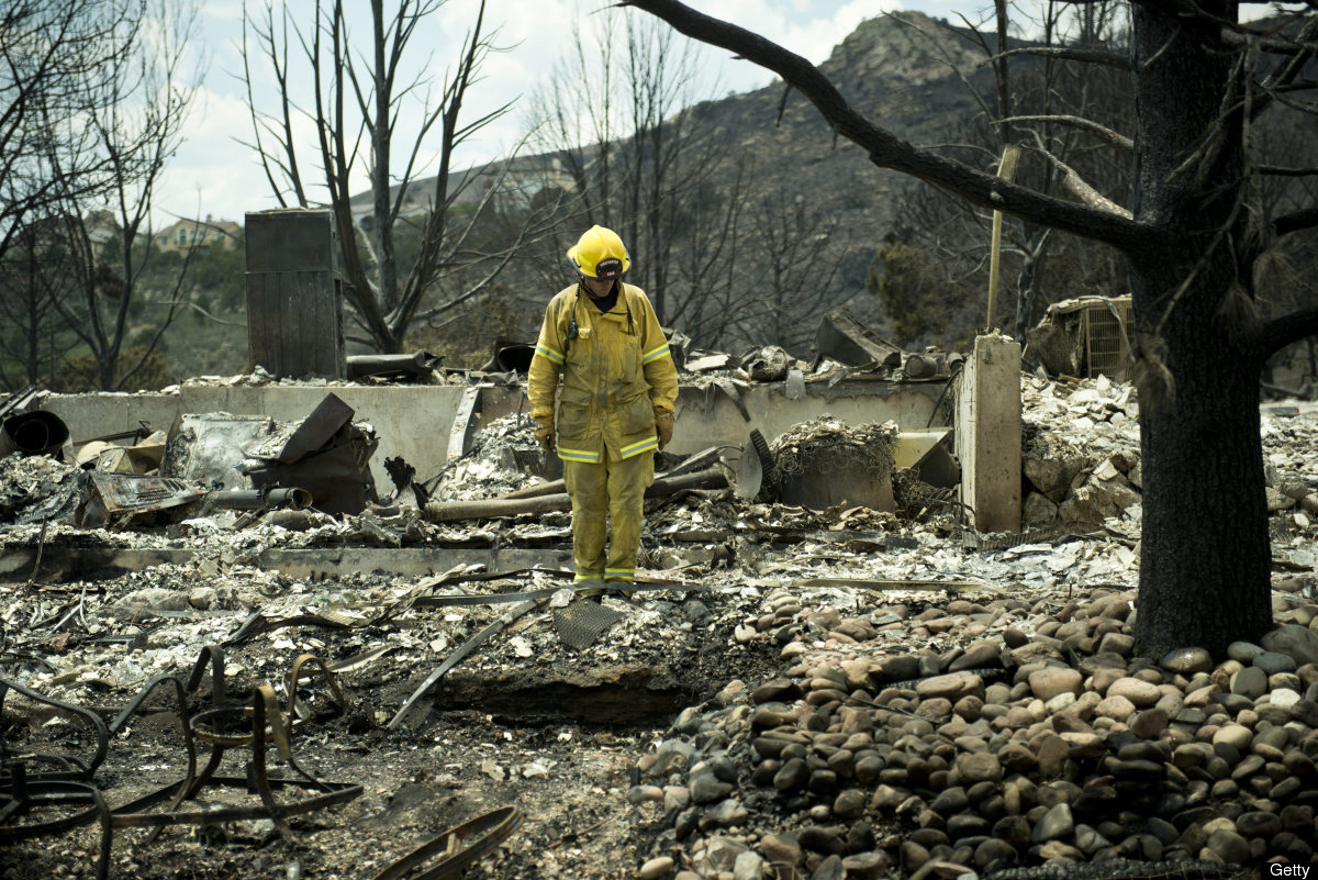 A firefighter stands in rubble in the Mountain Shadow neighborhood, which was burned by wildfires about 72 hours ago, on June