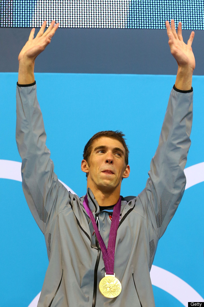 LONDON, ENGLAND - AUGUST 04:  Gold medallist Michael Phelps of the United States celebrates on the podium in the medal ceremo