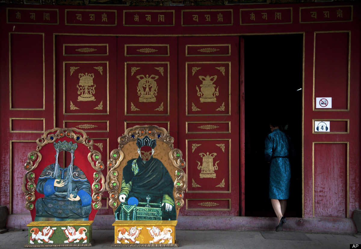 A Mongolian woman walks into a hall where faceless Buddha cutouts set up for souvenir pictures by tourists outside at the Cho