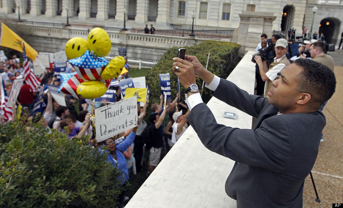 FILE - In this March 21, 2010 file photo, Rep. Jesse Jackson, Jr., D-Ill., uses his PDA to photograph demonstrators outside o