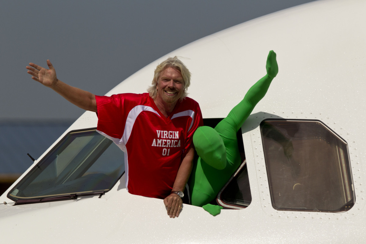 "Sir Richard Branson accompanied by Green Man from the TV show ""It's Always Sunny In Philadelphia"" waves during a ceremony mar"
