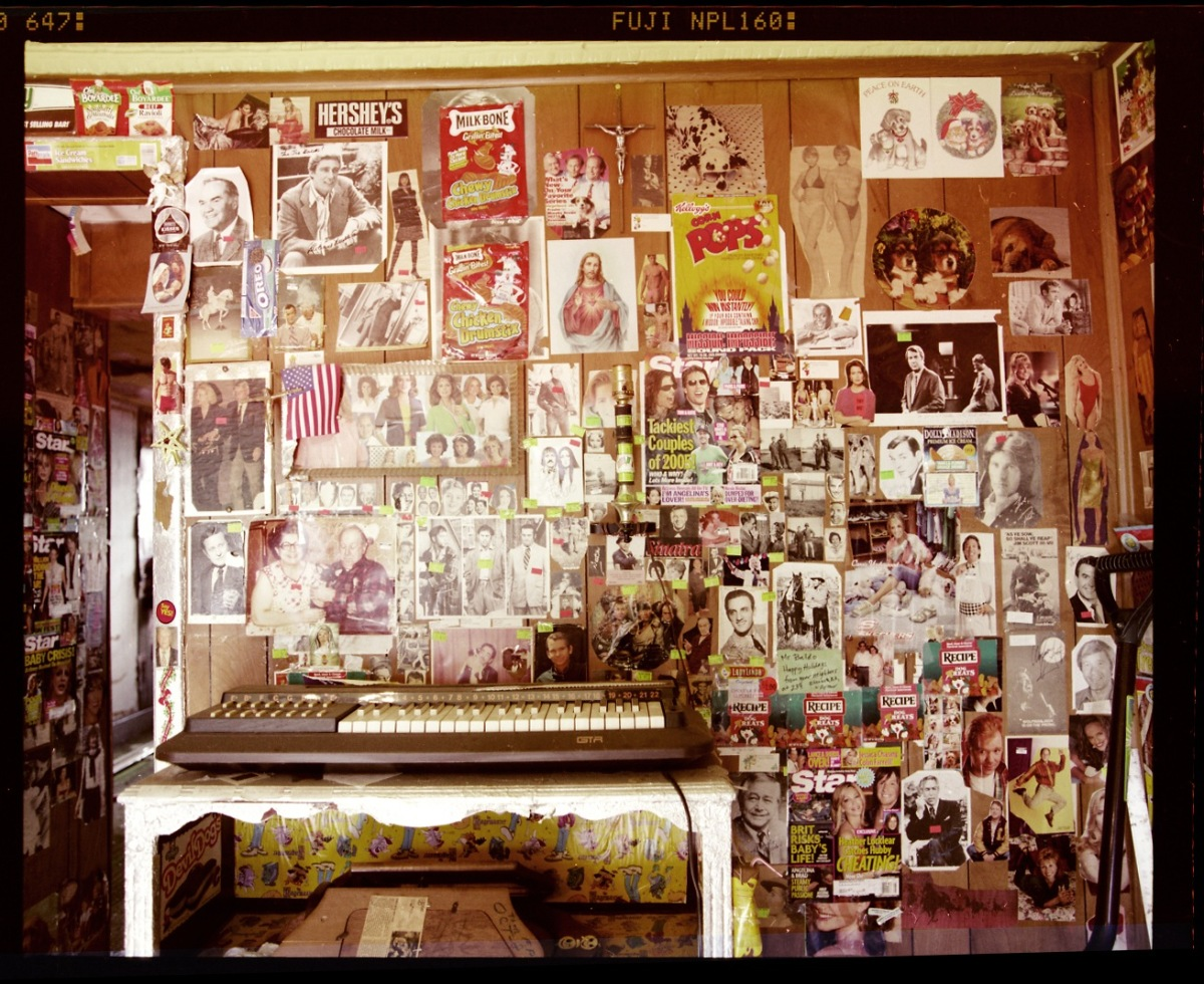 Above an electric keyboard, the eccentric homeowner plastered cardboard food packages, magazine covers, and other scraps.