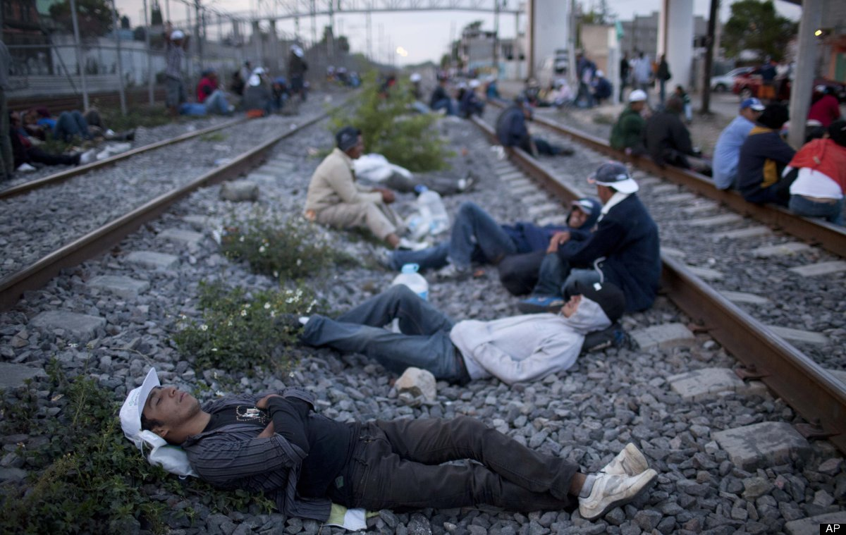 In this May 17, 2012 photo, migrants, mostly from Honduras, rest on railroad tracks as they wait for a train headed north, in