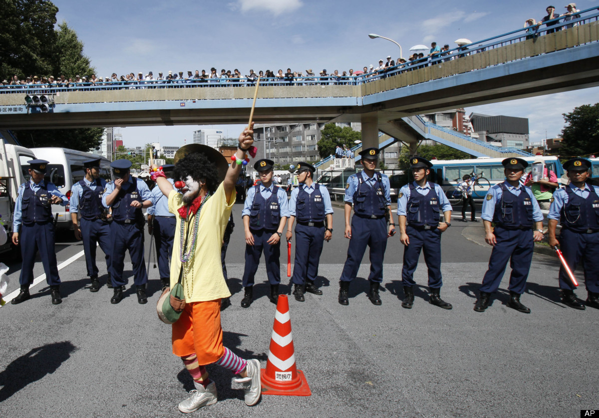 An anti-nuclear protester dressed as a clown is watched by police officers during a rally in downtown Tokyo Monday, July 16,