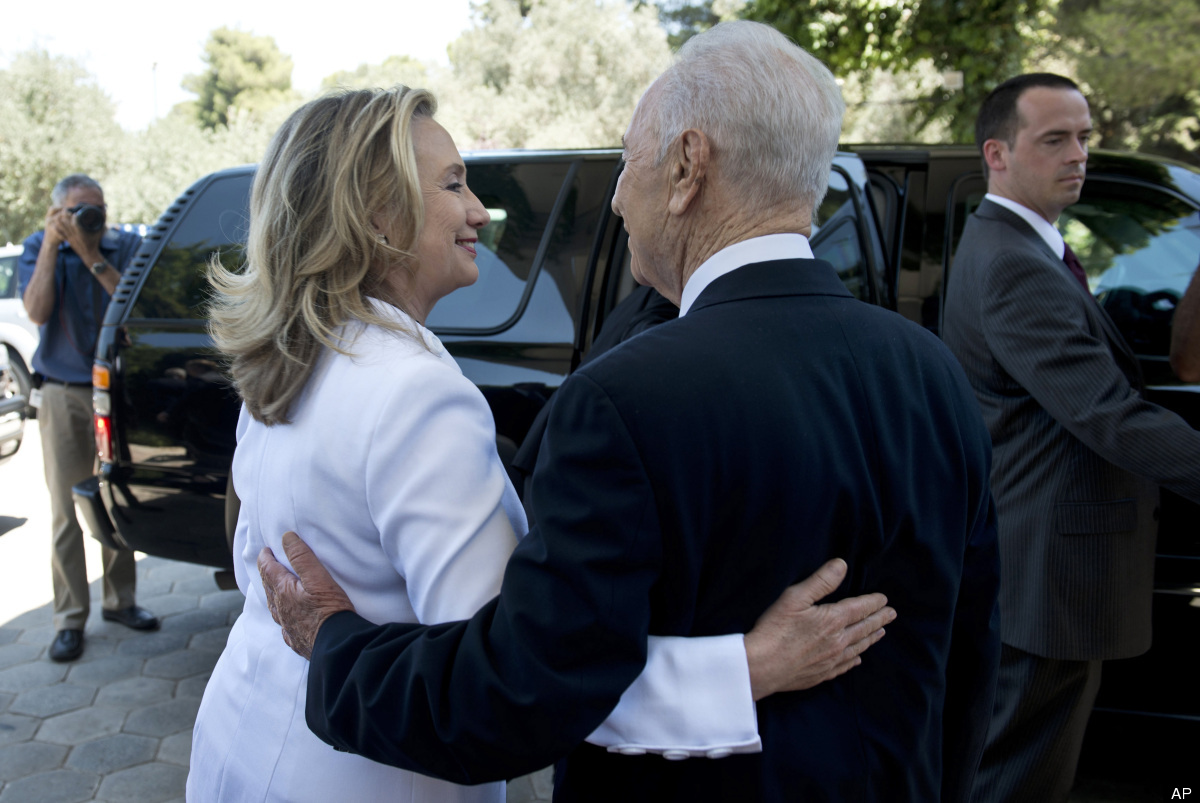 Israel's President Shimon Peres, right, walks US Secretary of State Hillary Rodham Clinton, left, to her car following their